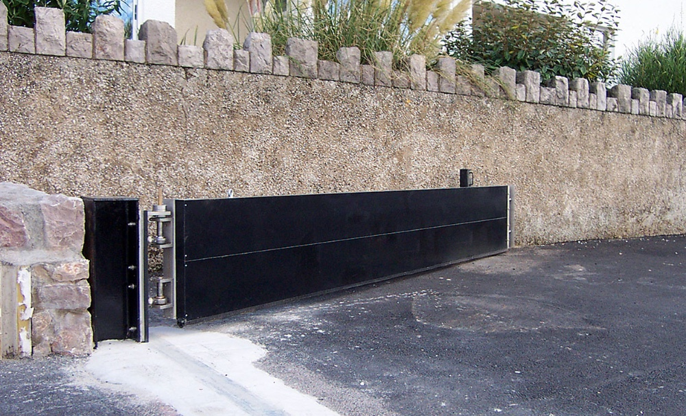 Lift-hinged flood gate gives permanent flood defence,  rapid deployment and vehicle access.